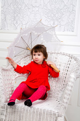 little girl in red dress in studio with umbrella