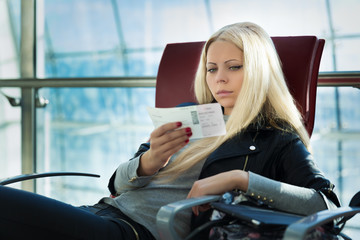 Young pretty blonde woman with air travel tickets sitting in arp