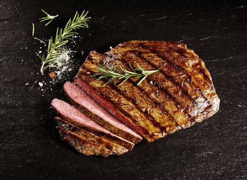 Roasted medium rare sliced flank beef with rosemary