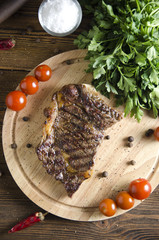 grilled beef steak on wooden board on wooden background