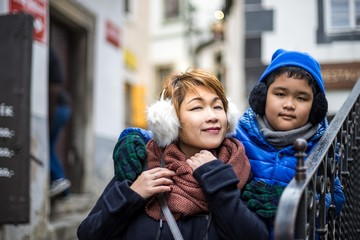 Asian boy and mom infront of the  old city Cesky Krumlov castle