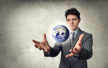 Young businessman with planet that floats out of the hands