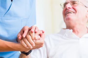 Altenpflegerin hält Hand von Senior in Altersheim
