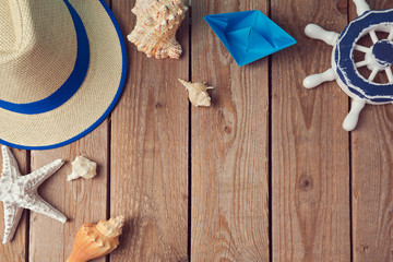 Summer holiday travel background with seashells and paper boat. View from above. Flat lay