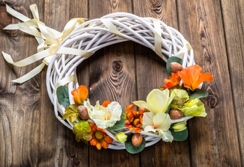 Wreath with easter eggs and flowers on wooden background