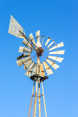 Old rusty windmill with some broken blades