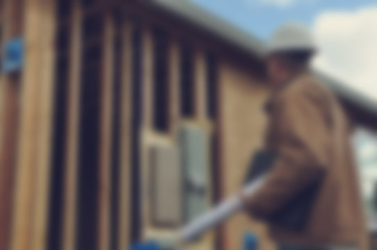 Blurred Construction Worker Inspecting Home Construction Site wi