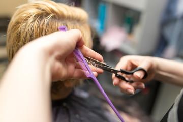 Female hair cutting scissors in beauty salon