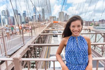 Wall Mural - Beautiful young Asian woman portrait on Brooklyn bridge, New York city NYC, Manhattan, USA. Smiling tourist in blue dress doing summer travel in urban landmark.