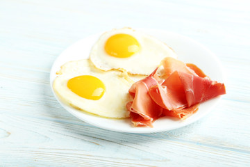 Fried eggs with bacon on plate on blue wooden table