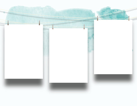 Close-up of three hanged paper sheets with pegs on cyan paint brush stroke background