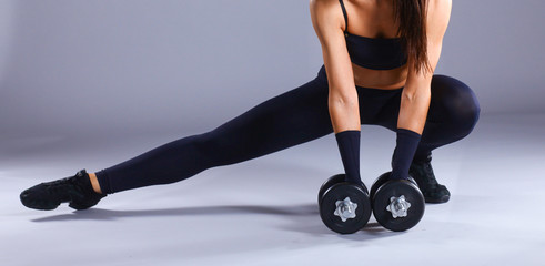 Athletic woman pumping up muscles with dumbbells and stretching legs