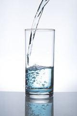 Concept of drinking. Pouring water from into glass