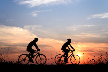 Silhouette of cyclist with friend motion on sunset background