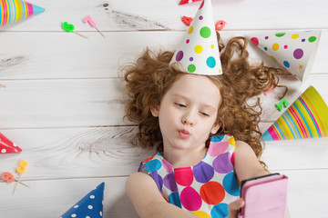 Little girl on wooden floor making selfie photo in birthday part
