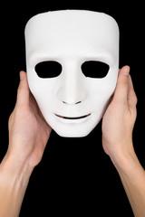 Hands holding white mask on black background.