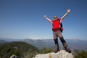 Hiker standing on top of the mountain with valley on the background.