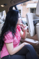 Asian woman sits on the luxury car