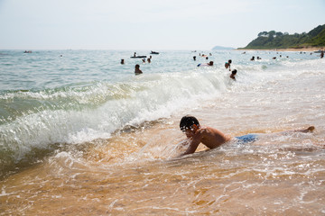 Boy swims in the surf