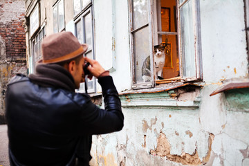 Man taking a picture of a cat