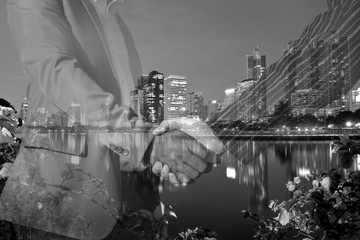 double exposure of handshake and the city - black and white
