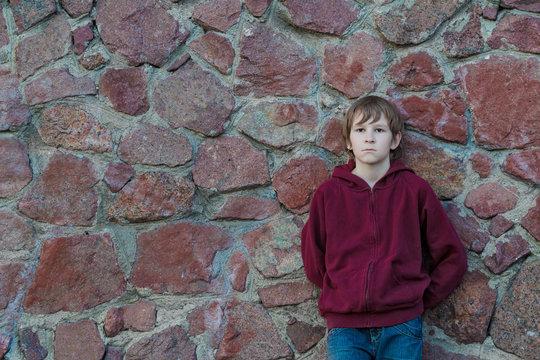 Teenage boy wearing burgundy hooded sweatshirt with vertical zipper leaning red granite boulders wall