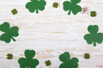 Fabric green clover leaves on wooden background.
