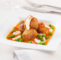 Meatballs with squid and green peas in sauce.