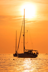 Yacht in the sea at sunset hot yellow light - seascape background, vertical shot