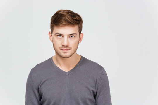Portrait of serious handsome young man in grey pullover