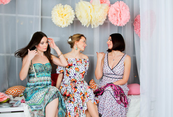 Three young, beautiful and emotion girls in bright colored dress. They talk to each other. Spring mood. Girls gatherings.