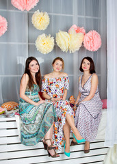 Three young beautiful girls in bright colored dresses. Spring mood. Girls gatherings.