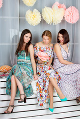 Three young beautiful girls in bright colored dresses. Decoration flowers. Spring mood. Girls gatherings.