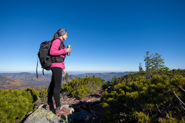 Young woman backpacker reaching her goal standing on peak of the mountain, holding cup of coffee and enjoying the beautiful landscape. Sunny autumn time.