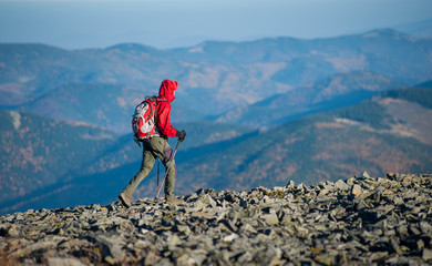 Male hiker backpaker walking on the rocky mountain ridge with beautiful mountains on background. Man is wearing red jacket and has trekking sticks and backpack on. Sunny fall day.