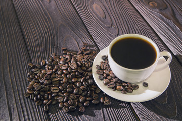Cup of coffee on wooden background with coffee beans