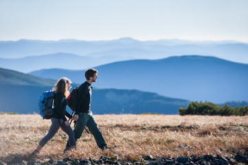 Young couple is walking in the mountains with backpacks. Side view with big beautiful mountains on the background. Travelers holding hands and looking into distance.
