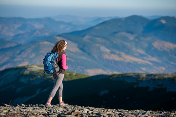 Young woman tourist is climbing down on mountain plato with big backpack on. Beautiful mountains on background. Sunny autumn day.