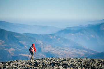 Climber is walking on the rocky mountain plato on backpacking trip. Beautiful mountains on background. Rear view. Ecotourism and healthy lifestyle concept. Copy space.