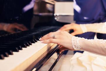 newlyweds play on grand piano keys