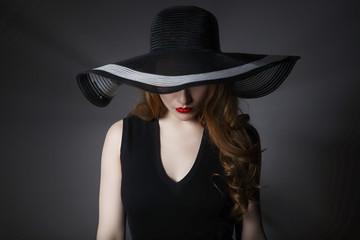 Portrait of elegant woman in black hat and dress.