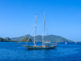 Sailboat navigates in the waters of the Archipelago of Les Saintes, Guadeloupe in the blue carribean sea.