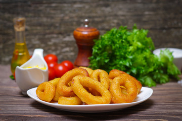 deep fried calamari with sauce and salad on a wooden background
