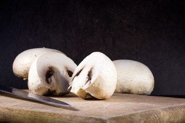 Champignon mushrooms on cutting board and dark background