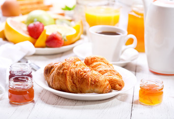 Breakfast with croissants, coffee, orange juice, toasts and frui