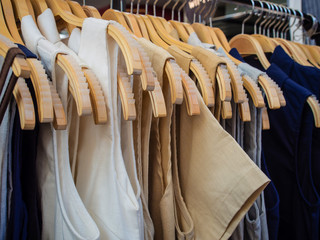 fashion clothes of different colors on wooden hangers