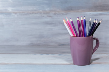 Stack of pink blue and purple colored pencils in a glass on wooden background