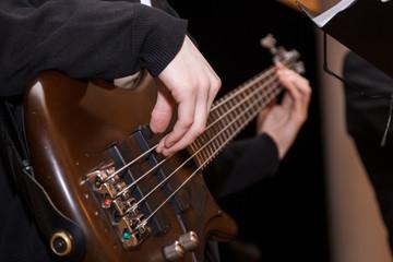 кисти рук и пальцы играют на бас гитаре