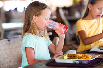 Adorable little girl having lunch in outdoor cafe