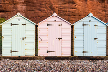 Beach hut row in pastel colors, red rock background
